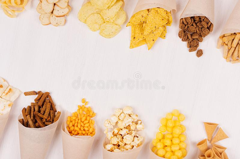 Summer fun fast food - different crunchy snacks in craft paper cornet as decoration border on soft white wood board. Summer fun fast food - different crunchy stock images