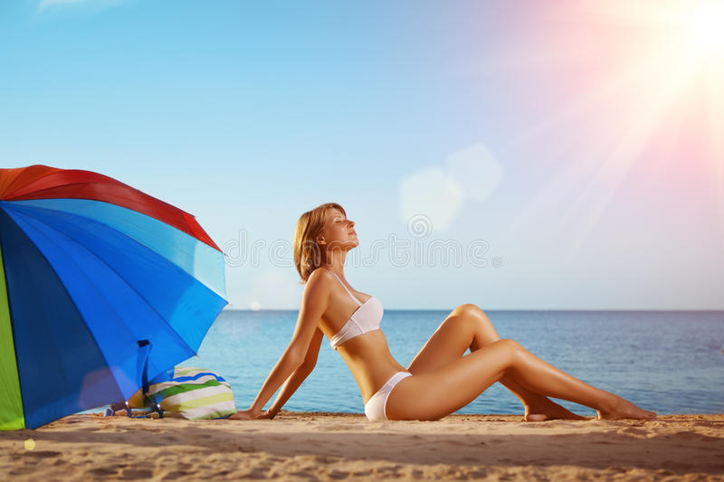 Summer fun holiday woman on summer landscape with rainbow umbrella. Girl with tanned body lying on the beach under the sun and bl royalty free stock image