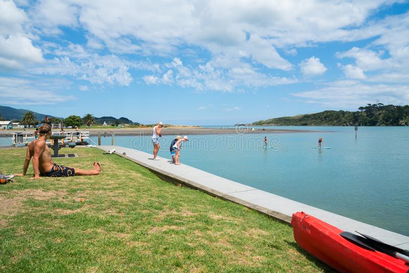 Summer fun in Raglan children fishing with mother on harbour edge while man sits in sun. RAGLAN, NEW ZEALAND - JANUARY 14, 2018; Summer fun in Raglan children royalty free stock images