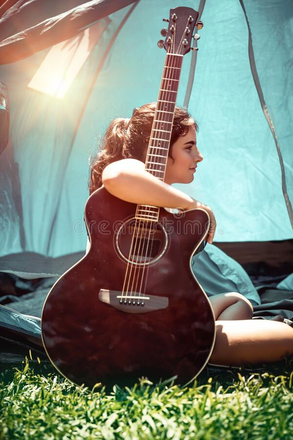 Summer fun. Teen girl with pleasure spending holidays in summer camp, pretty child sitting with a guitar near the tent, singing song and having fun in sunny royalty free stock photo
