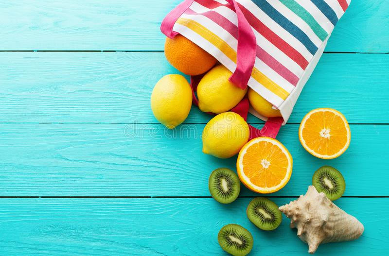 Summer fun time and fruits on blue wooden background. Mock up and picturesque. Orange, lemon, kiwi fruit in bag and shell. On the table. Top view and copy space royalty free stock photos