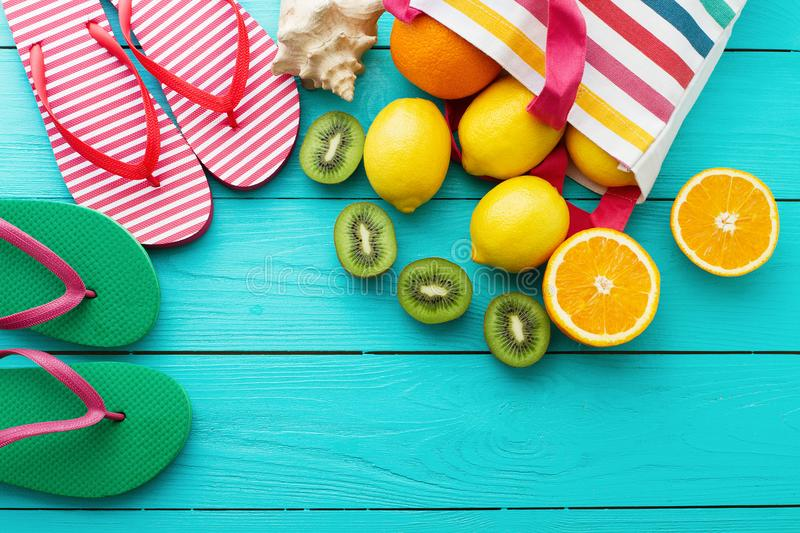 Summer fun time and fruits on blue wooden background. Orange, lemon fruit in bag and flip flops. Top view and copy space stock images