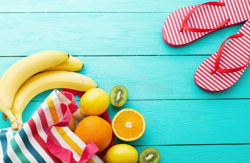 Summer fun time. Fruits on blue wooden background. Orange, lemon, kiwi, banana fruit in bag and flip flops on the floor. Top view stock image