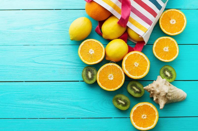 Summer fun time and fruits on blue wooden background. Orange, lemon, kiwi fruit in bag and shell. On the table. Top view and copy space. Mock up royalty free stock images