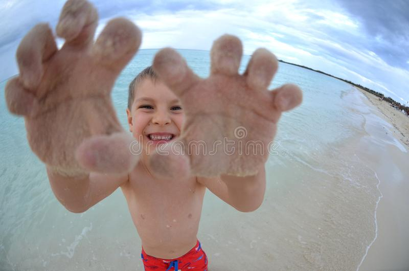 Portrait of a handsome young Caucasian boy playing on a beach on vacation in a tropical travel destination stock photos