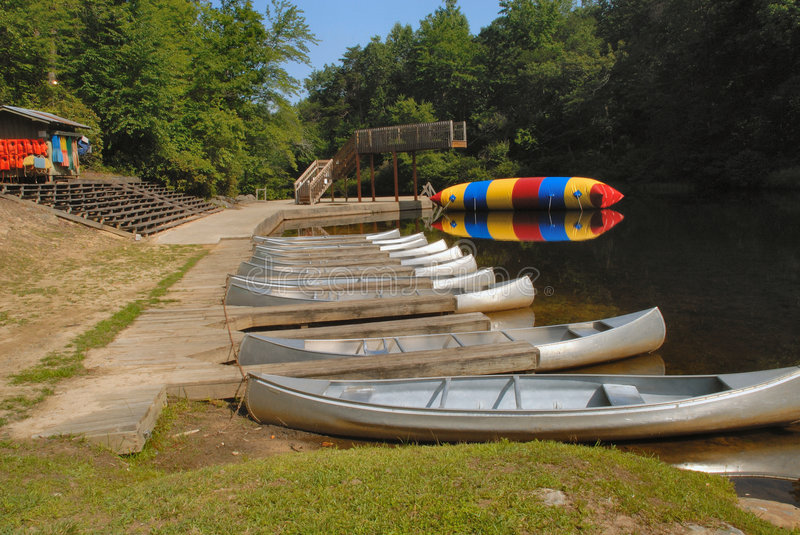 Summer fun at the waterfront. Summer fun at the waterfront with canoes, boating, bouncing, swimming and playing at camp royalty free stock image