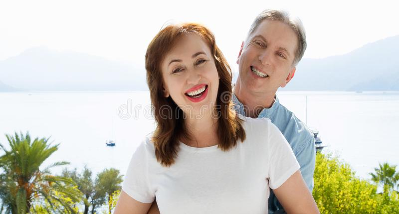 Summer fun weekends at tropical beach. Happy middle aged family couple on nature sea background. Healthy relationship and love royalty free stock image