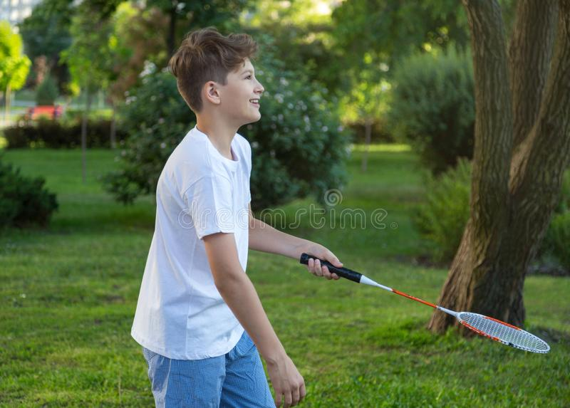 Summer funny portrait of cute boy kid playing badminton in green park. Healthy lifestyle. Concept stock photos