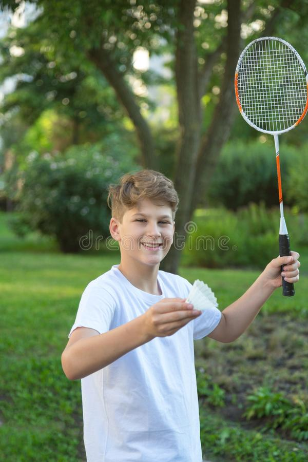 Summer funny portrait of cute boy kid  playing badminton in green park. Sport, Healthy lifestyle royalty free stock photo