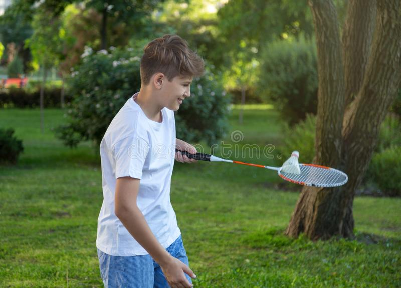 Summer funny portrait of cute boy kid  playing badminton in green park. Sport, Healthy lifestyle. Concept royalty free stock image