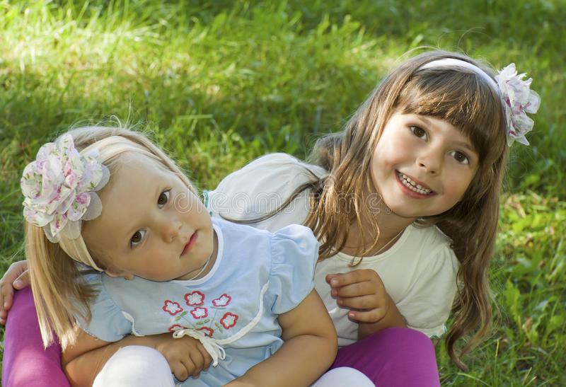 Summer games on a grass. Girls sit in the summer on a grass and play royalty free stock image