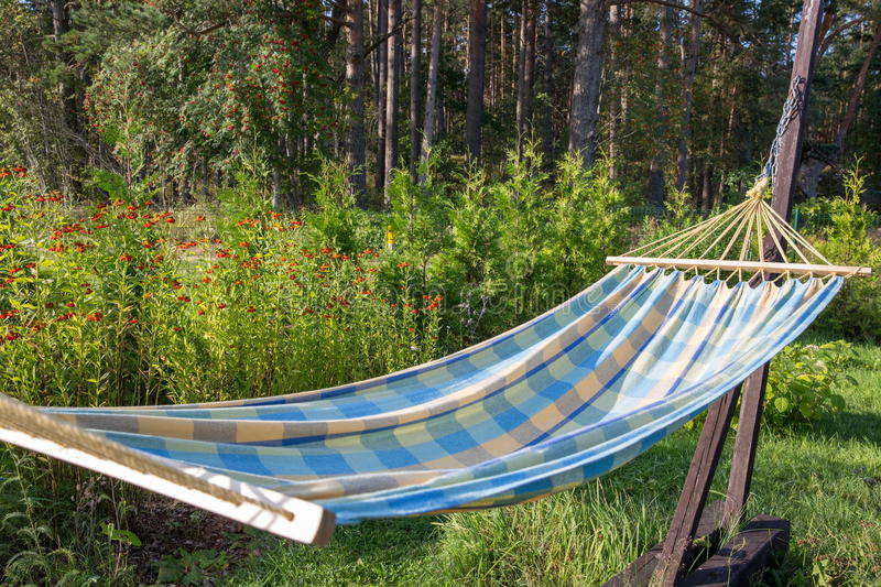 Summer garden with hanging hammock for relaxation stock images