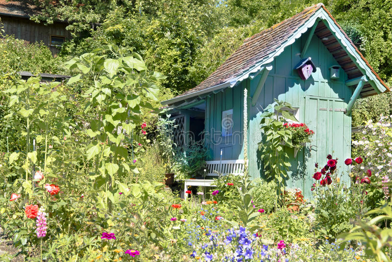 Wooden turquoise summerhouse in beautiful summer garden. Summer garden with lots of flowers and small summerhouse in Germany royalty free stock photos