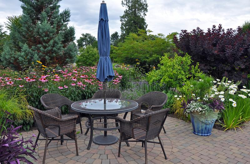 Summer garden patio. Lovely garden patio with table and wicker chairs stock photo