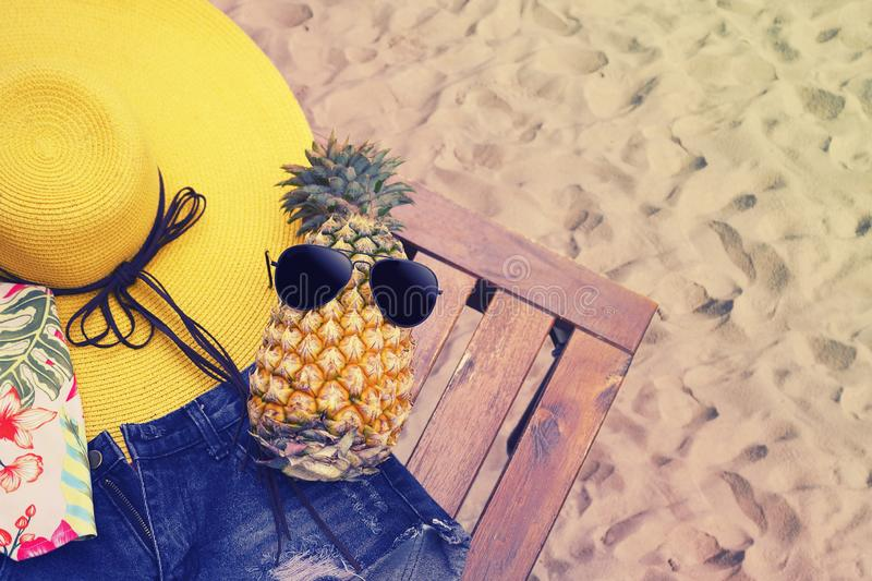 Summer girl clothes set, Accessories on beach background. Fashion colorful stylish dress, sunglasses on pineapple. Flat lay. stock photography