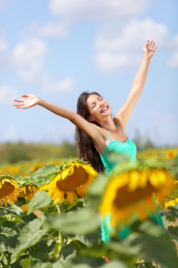 Summer girl happy in sunflower flower field. Cheerful multiracial Asian Caucasian young woman joyful, smiling with arms raised up royalty free stock photo