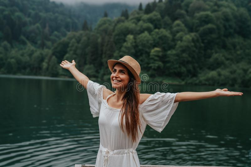 Summer girl portrait. Young woman smiling happy on sunny summer or spring day outside in park by lake. stock photography
