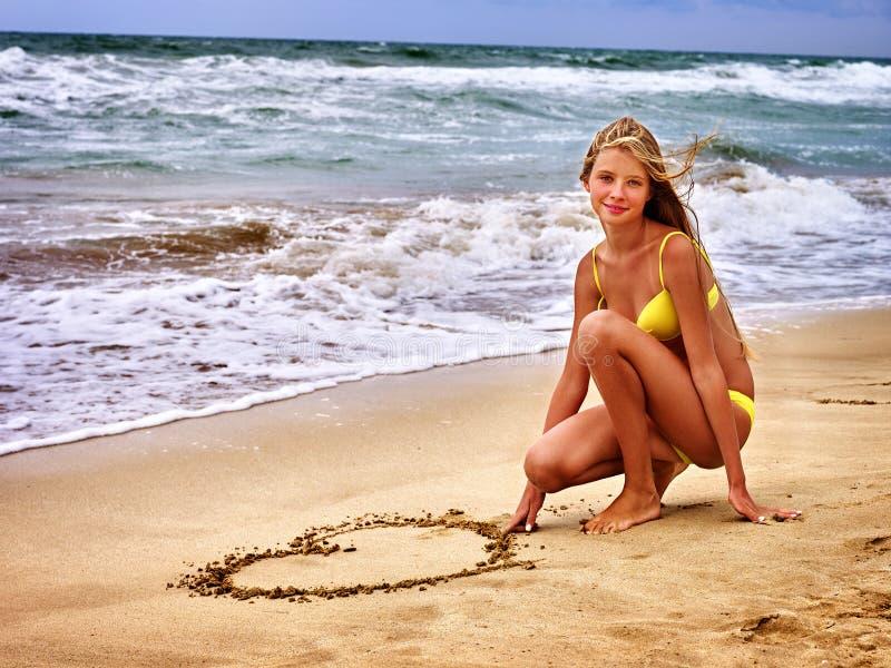 Summer girl sea. Girl in swimsuit write on sand heart shape . stock photo