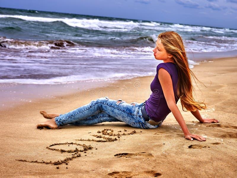 Summer girl sea look on water. Summer girl sea. Girl draw love word on sand on sea beach royalty free stock photography