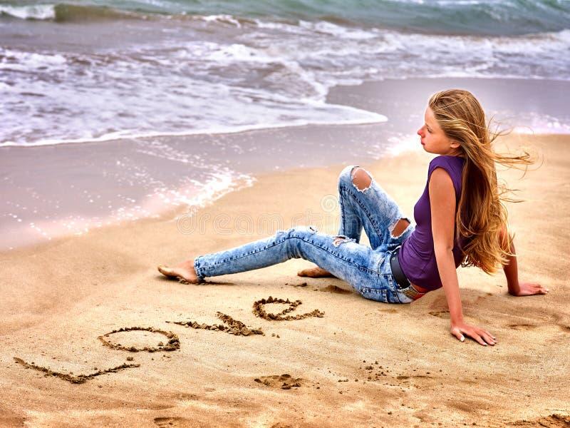 Summer girl sea look on water. Summer girl sea. Teenager writing love on sand stock photos