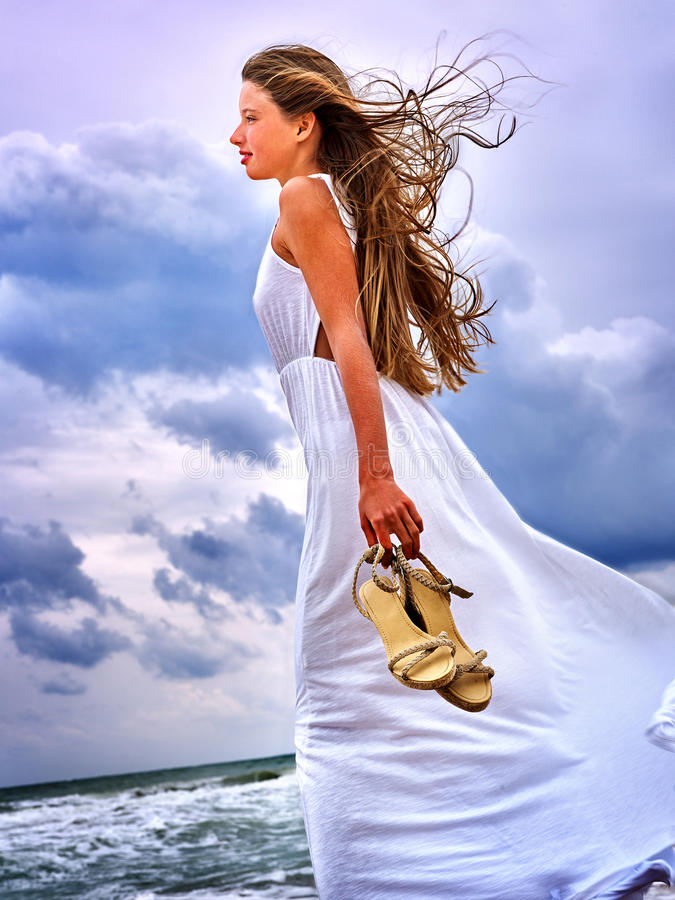 Summer girl sea look on water. Summer girl sea. Woman with footwear in hands going on coast stock images