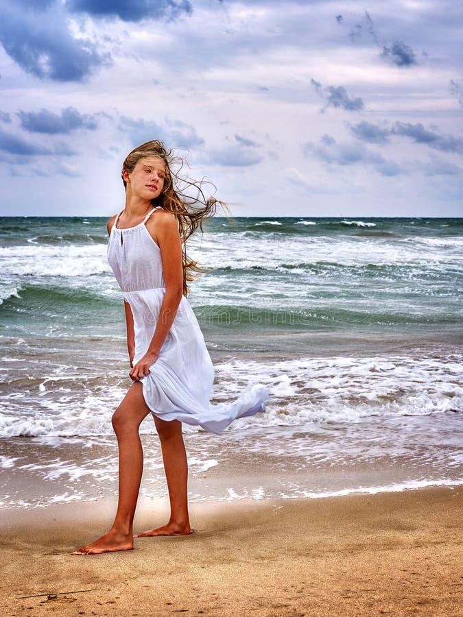 Summer girl sea look on water. Summer girl sea. Woman wearing white sundress goes on coast stock photos