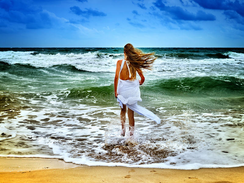 Summer girl sea. Woman goes at water on coast. Girl came out of sea foam. Female with long hair in white sundress walking barefoot on seawater beach. Blue sky royalty free stock photo