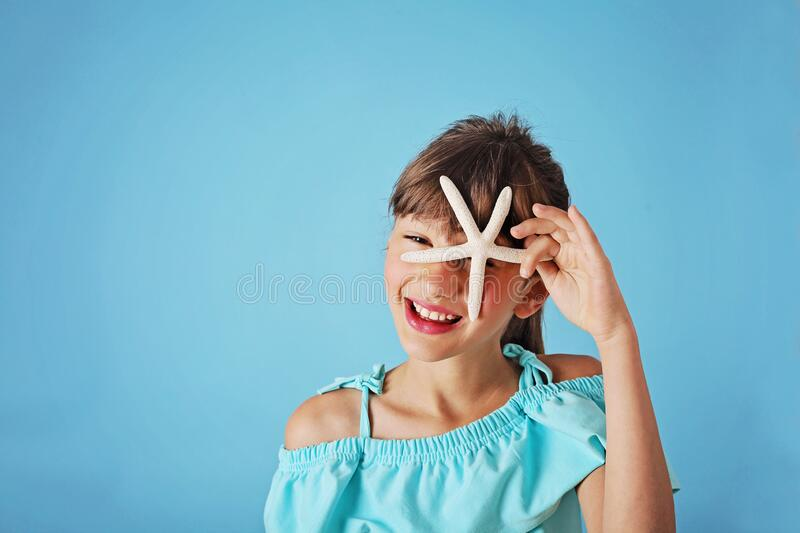 Summer girl. Smiling cute girl with seashell in the studio stock photography