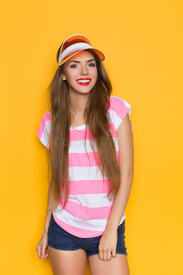 Summer Girl In Sun Visor. Smiling young woman in pink stripped shirt, jeans shorts and orange sun visor. Three quarter length studio shot on yellow background stock photos