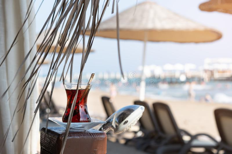 Summer, a glass of tea, on the beach, against the background of the sea. The concept of summer holidays and vacation stock photo