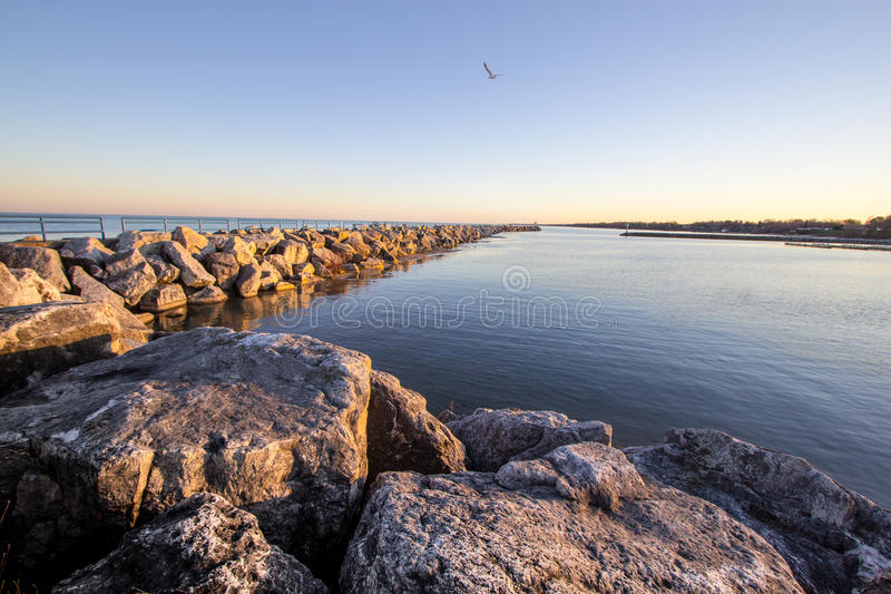 Summer On The Great Lakes Shore. Coastal Great Lakes harbor bathed in the golden glow of the warm summer sun. Tierney Park. Lexington, Michigan stock photo