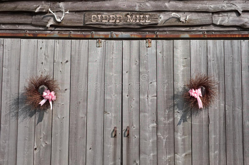 Summer handmade wreaths hanging on old barn doors royalty free stock images