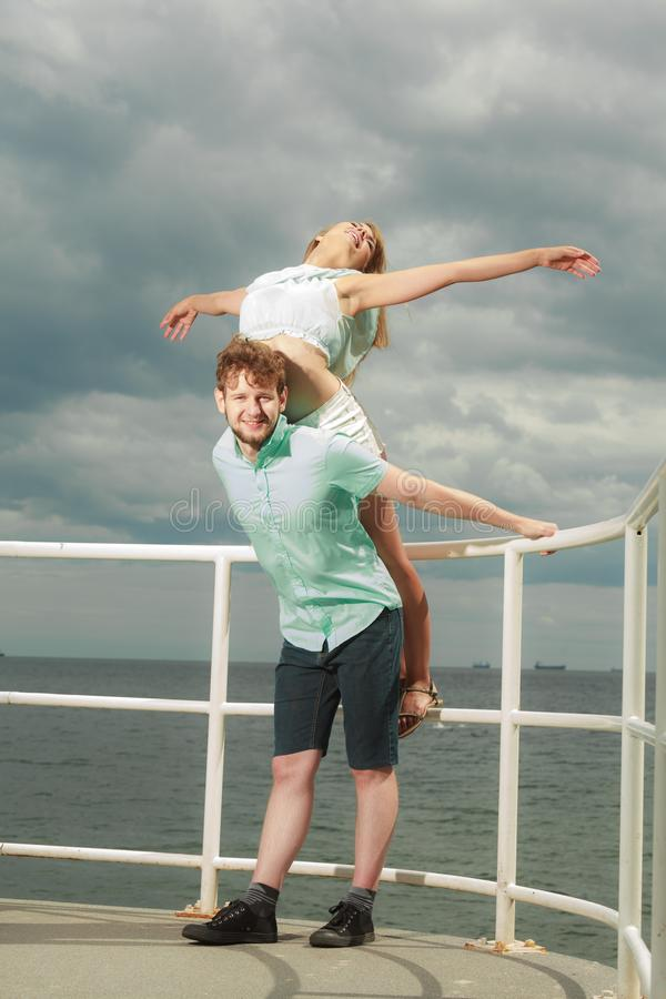 Couple in love having fun on sea pier. Summer happiness concept. Woman and men young couple in love playing sharing free time having fun outdoor on sea pier sky stock image