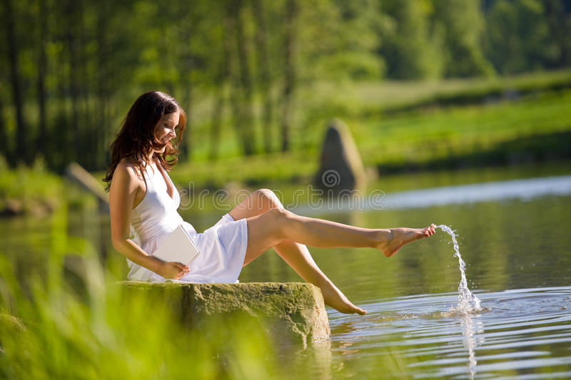 Summer - Happy romantic woman sitting by lake stock image
