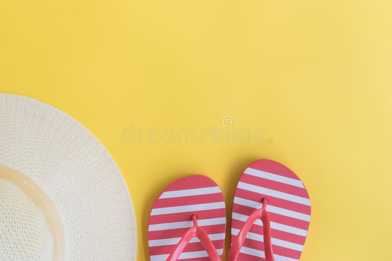 Summer hat and flip flops. On a yellow background. Top view, flat lay stock photography