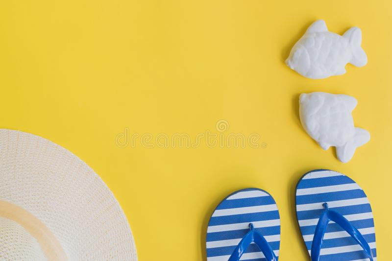 Summer hat and flip flops. On a yellow background. Top view, flat lay royalty free stock images