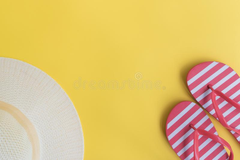 Summer hat and flip flops. On a yellow background. Top view, flat lay stock image
