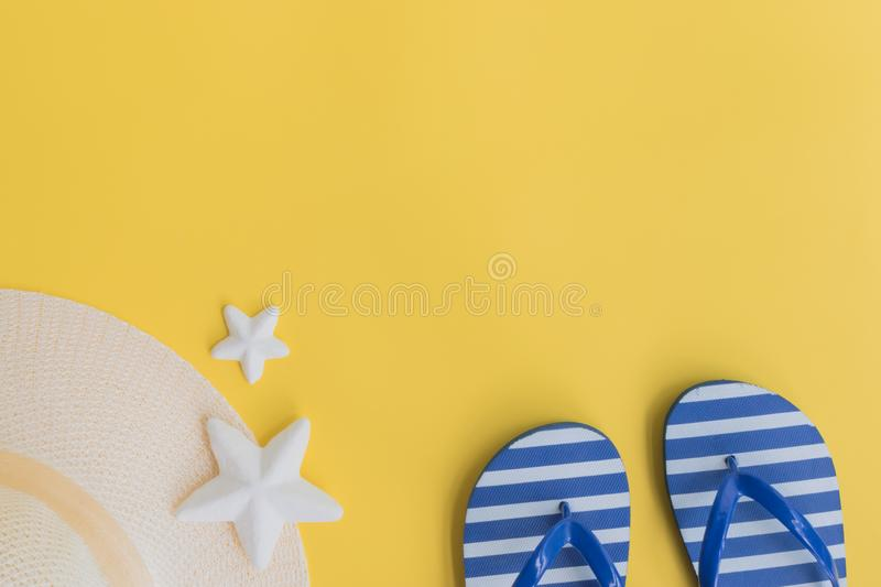 Summer hat and flip flops. On a yellow background. Top view, flat lay stock images