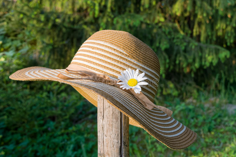 Summer hat in the garden. A summer hat in the garden on a wooden slat stock image
