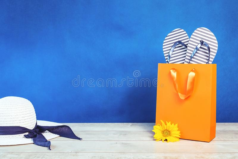 Summer hat orange bag and flip flops on blue background royalty free stock photos