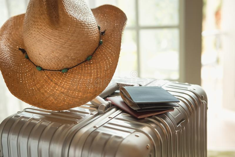 Summer hat, purse and passport on a silver suitcase, close up, selective focus. Travel, vacation, lifestyle theme royalty free stock photos