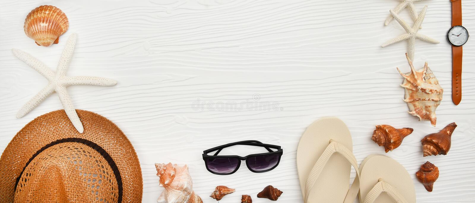 Summer hat and sunglasses with sandals and shells stock photos