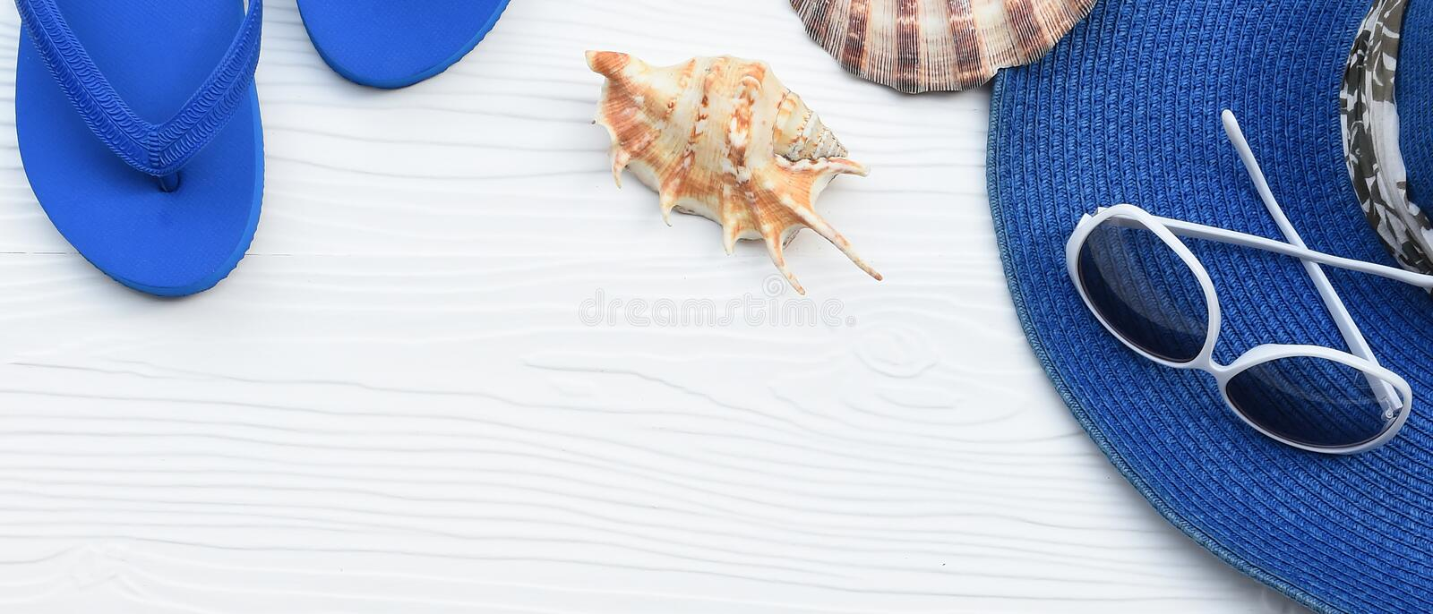 Summer hat and sunglasses with sandals and shells royalty free stock photo