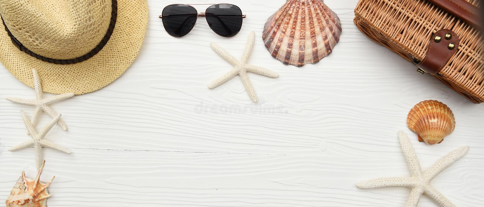 Summer hat and sunglasses with sandals and shells stock images
