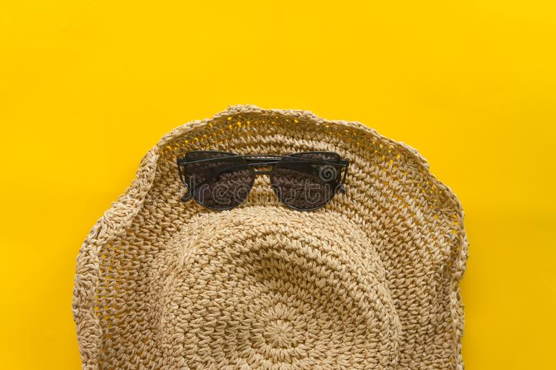 Summer hat weave and sandal weave with yellow background. Put on the summer stock photo