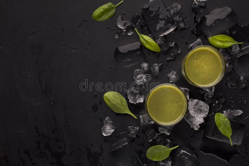 Summer healthy cocktails in glasses on black background. Summer healthy cocktails in glasses on black refreshing background with ice cubes and copy space royalty free stock photo