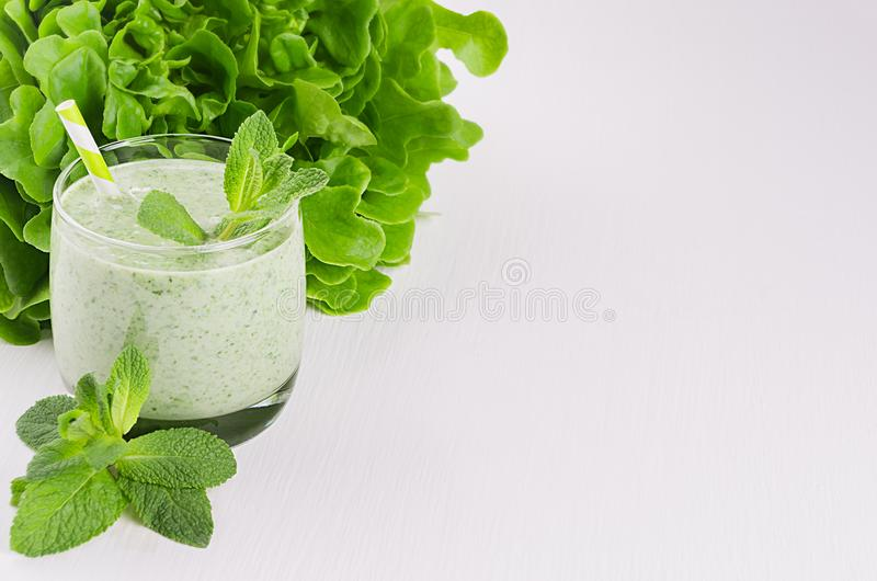 Summer healthy food - green vegetable smoothies with leaf mint, greens, straw on white wood background. Summer healthy food - green vegetable smoothies with royalty free stock image