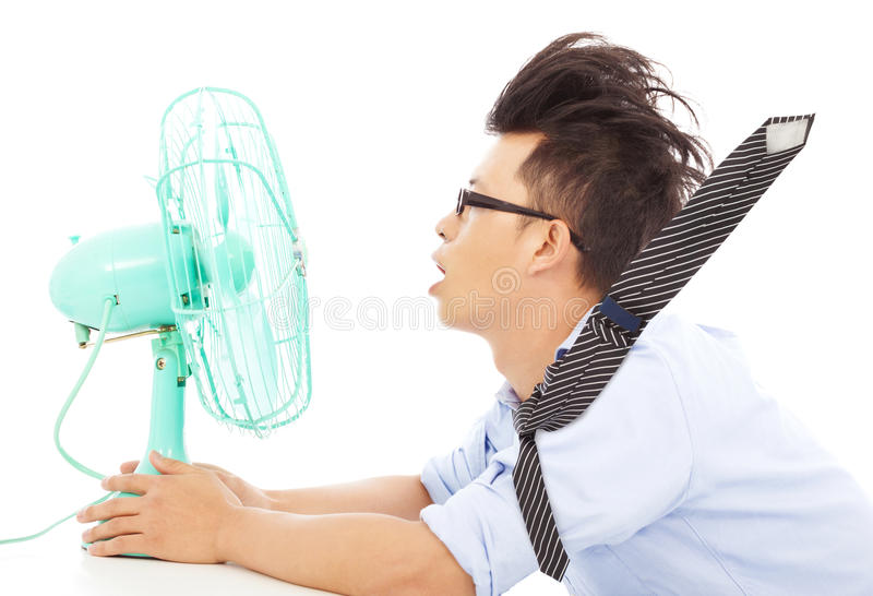 Summer heat, business man use fans to cool down stock images