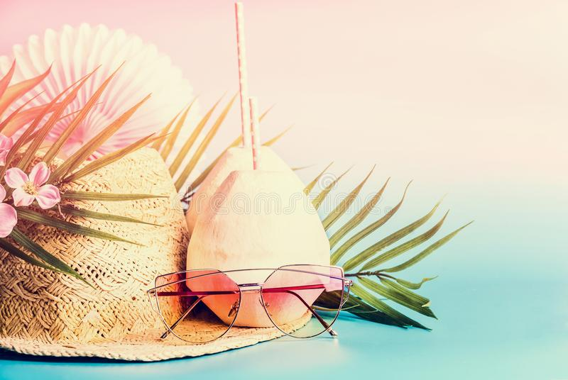 Summer holiday accessories: straw hat, coconut drinks, sunglasses. palm leaves and flowers at sunny background, front view, place stock images