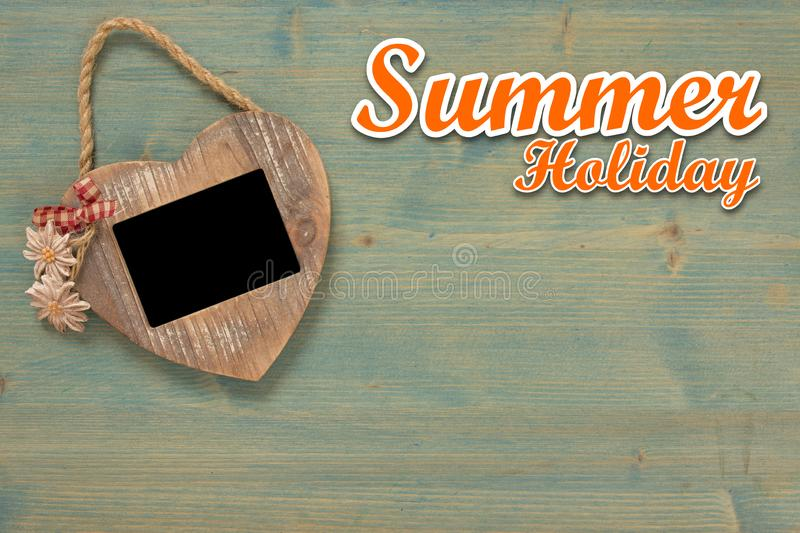 Summer holiday background with text.  Heart, frame on black photo on rustic wooden wall with copy space royalty free stock image